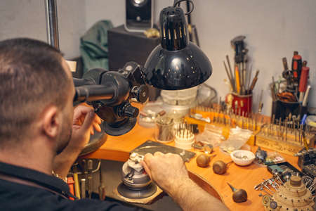 Back view of a craftsman using an optical tool for treating a metal piece of jewelry Imagens