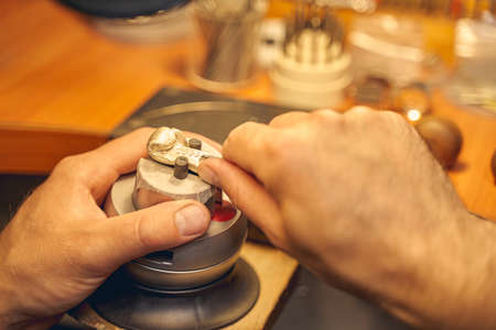Close up of Caucasian male jeweler hands using a graver for making a new metal pendant Imagens