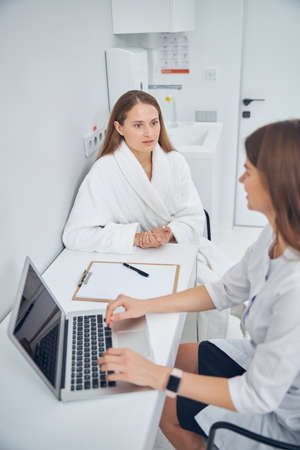 Close up portrait of beautiful woman in the white soft robe looking at her nutritionist while doctor working on the laptop Banque d'images