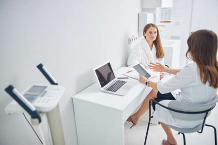Portrait of two women sitting in the white medical room while discussing something about the health