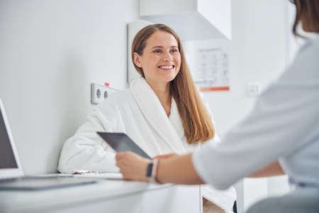 Close up portrait of cheerful patient of beauty clinic while having dialog with cosmetologist
