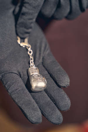 Cropped photo of a professional jeweler showing a boxing glove keychain pendant in front of the camera
