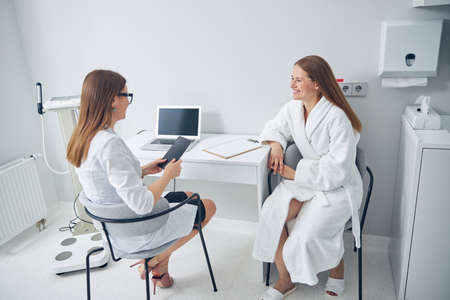Happy lady wearing soft bathrobe having conversation with her specialist in beauty center