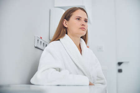 Seriously adult lady wearing white robe sitting at the bright clinic room