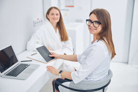 Woman beauty specialist in glasses having a productive day while working on modern laptop and tablet in her office