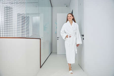 Full length portrait of young beautiful woman in the white silk bathrobe walking down the hall Banque d'images