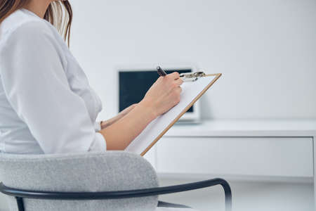 Cropped head portrait of professional doctor with clipboard in hand while working in clinic