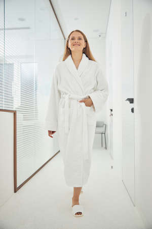 Full length portrait of lovely lady in soft bathrobe walking on the hall beauty clinic