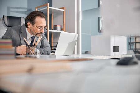 Bearded gentleman in glasses sitting at the table and working on notebook in office