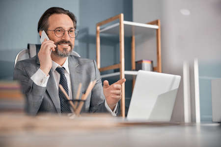 Handsome bearded man having phone conversation and smiling while sitting at the table in office Stock fotó