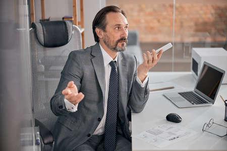 Bearded man using speakerphone while talking on cellphone in modern office Stock fotó