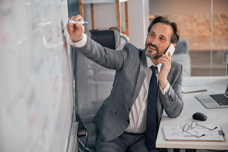 Handsome smiling man having phone conversation and writing on whiteboard while sitting at the table in office Stock fotó