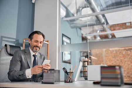 Handsome businessman checking messages on smartphone and smiling while sitting at the table with laptop in office Stock fotó