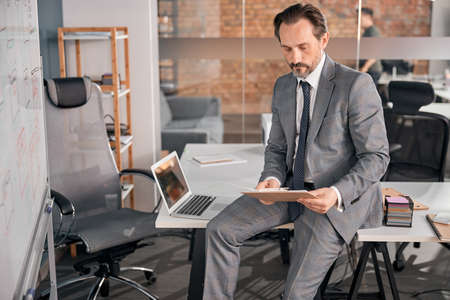 Handsome businessman in stylish suit sitting on office table and holding clipboard with papers Stock fotó