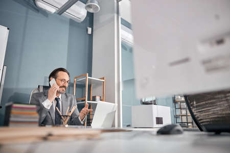 Handsome bearded man having phone conversation and smiling while sitting at the table with notebook in modern office Stock fotó