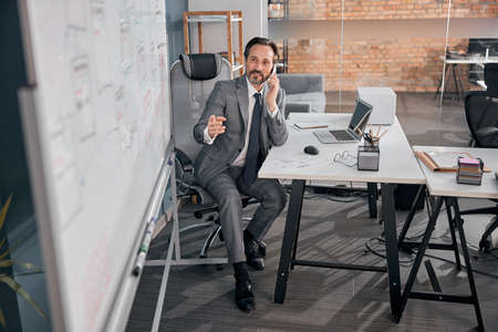 Cheerful bearded man having phone conversation and smiling while sitting at the table with laptop in modern office Stock fotó