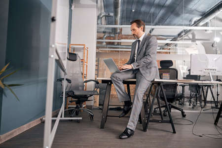 Handsome bearded man in gray suit sitting on office table and working on notebook