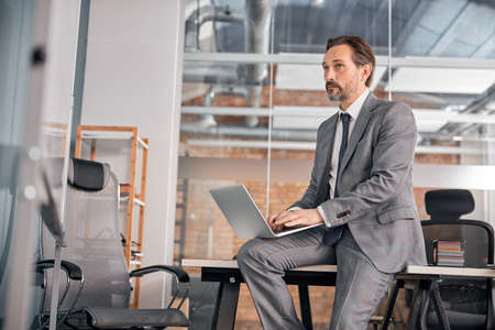 Serious bearded man in gray suit sitting on office table and working on notebook