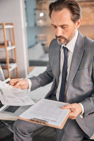 Serious gentleman in stylish suit working with papers while sitting on office table Banque d'images