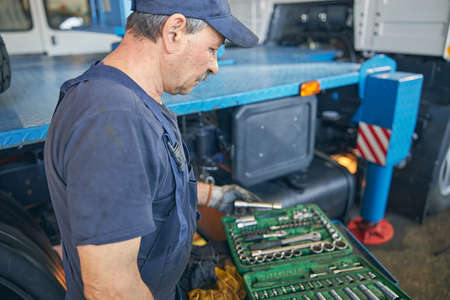 Close up of concentrated repairman holding set of instruments, standing in workshop in semi position