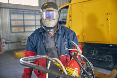 Busy welder wearing mask before working with dangerous instrument, holding fire extinguisher