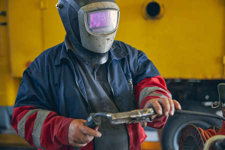 Attentive repairman wearing mask while working and welding metal details, being in workshop