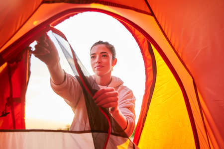 Attractive female traveler in sweatshirt unzipping touristic tent and smiling Stockfoto