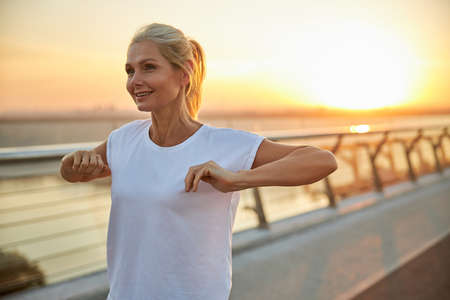 Waist-up portrait of a beautiful swarthy sporty woman in a t-shirt stretching her arms outdoors