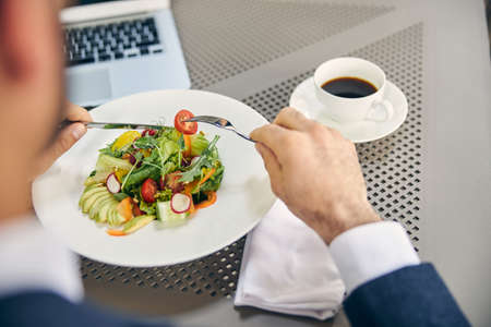 Focused photo on male person that using fork and knife while eating salad in cafe