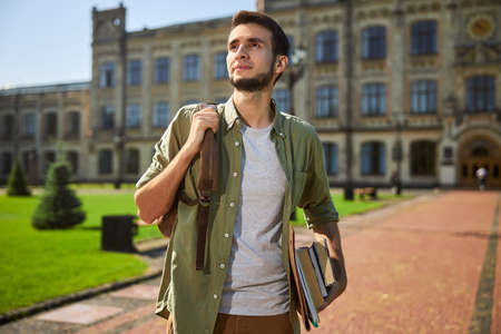 Dark-haired male student with books and a backpack in his hands gazing into the distance
