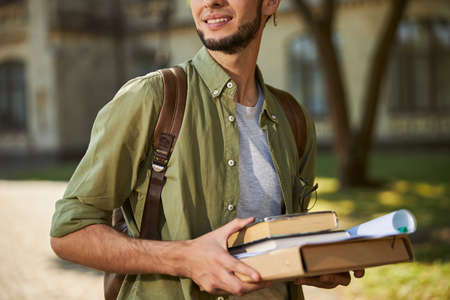 Cropped photo of a pleased young man with a dark beard holding a pile of books