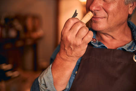 Close up of man in apron smelling cork of alcoholic drink in wine cellar