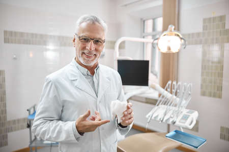 Cheerful elderly dental specialist holding and pointing to a big white tooth replica while explaining teeth anatomy
