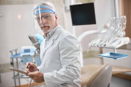 Attentive elderly dentist wearing a clear facial shield holding a pen and a clipboard while looking at the camera