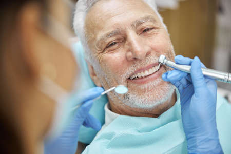 Close-up photo of a cheerful aged man smiling while having his teeth checked for caries and cavities