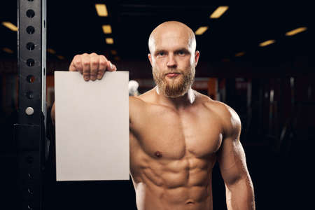 Copy space photo of a shirtless muscular man holding a blank white board and looking at the camera Archivio Fotografico