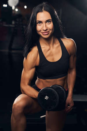 Cheerful brunette lady wearing workout gear and holding a dumbbell while flexing her muscles