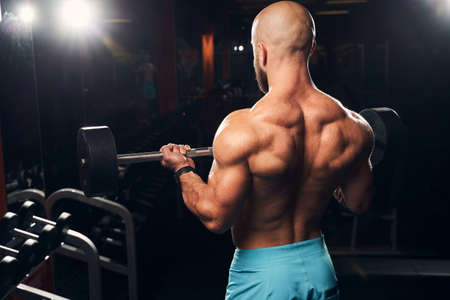 Waist-up photo of a strong sportsman lifting weights to exercise his back at the gym