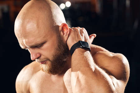 Close-up photo of a bald athletic man looking down and frowning while touching his neck