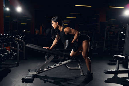 Hard-working fit woman lifting weights on an incline bench while exercising at the gym