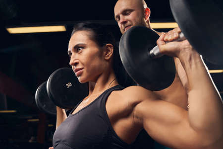 Strong beautiful woman holding a barbell with weights while working out with her friend Archivio Fotografico