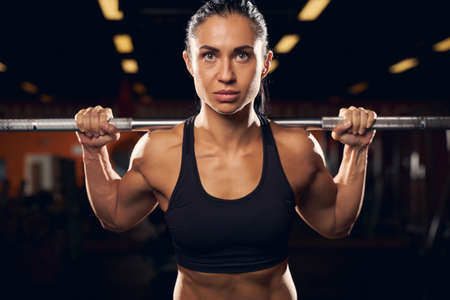 Close-up photo of a serious female athlete lifting weights on a barbell at the gym