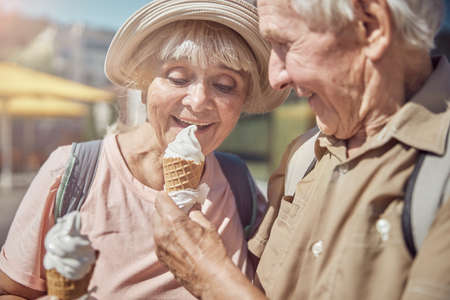 Pleased cute senior lady in a sunhat eating vanilla ice cream from her husband hand