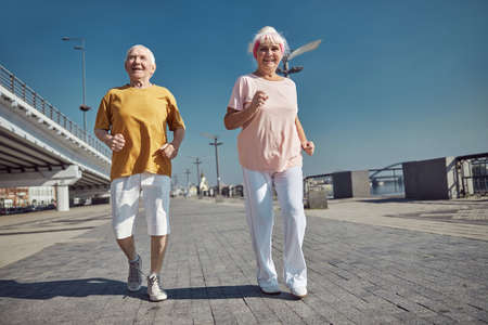 Full-length portrait of a high-spirited senior lady and her husband power walking along the quay