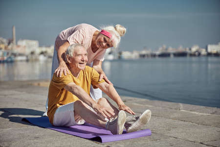 High-spirited pensioner performing a seated forward bend on the mat assisted by his cheerful wife