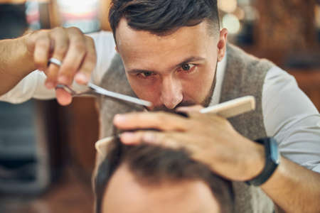 Focused professional barber taking a close look at hair of his visitor while working on his new cut