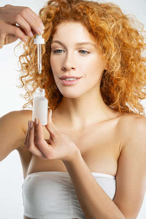 Gorgeous red hair woman looking at the bottle with nature cosmological drug oil for eyes