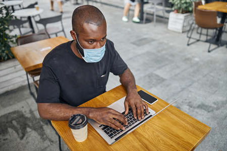 Young man wearing the medical mask while sitting at the cafe table with a modern laptop. Smartphone and a paper cup of coffee near