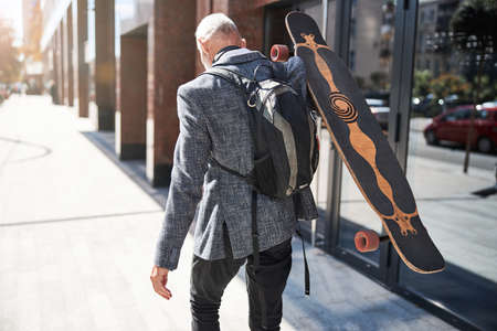 Back view of a senior citizen with a backpack carrying his longboard and walking Stock fotó