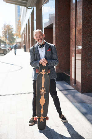 Full-length photo of a happy senior citizen holding his longboard and looking at the camera Stock fotó